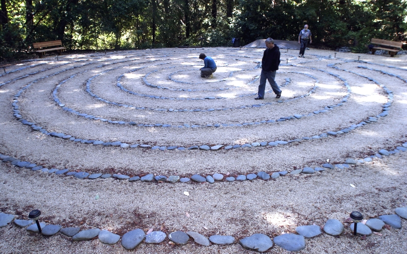 PHOTO BY LEN VAUGHN-LAHMAN SJ MERCURY NEWS SEPT 20 2004 (w/ LABYRINTH REvans) Nestled in the woods away from the Quaker Conference Center in the mountains outside of Ben Lomond, a newly consturcted labyrinth, made of simple gravel and river rock, opens in a clearing. The brainstorm of Tom Davis (background, right) , a member of the group, his permamnent creation replaces on made of rop. The labyrinth allows prayerful meditation around a predestined course, with one way in and out. Members Traci and Walter Hjelt Sullivan (cq\'d, no hyphen in last name) are on the labyrinth with Davis.